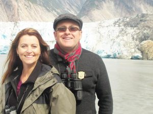 Laura Sable and Bill Wiemuth standing on a boat in Alaska. They offer virtual cruises.