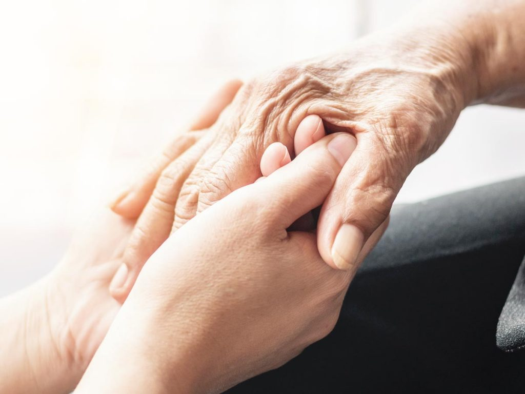 Photograph of old and young hands holding each other