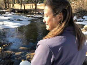 photo of Deborah Goslin sitting by a river in winter, absorbing sunlight with her eyes closed.