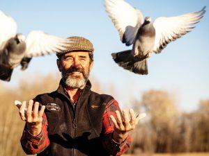 photo of senior man launching racing pigeons