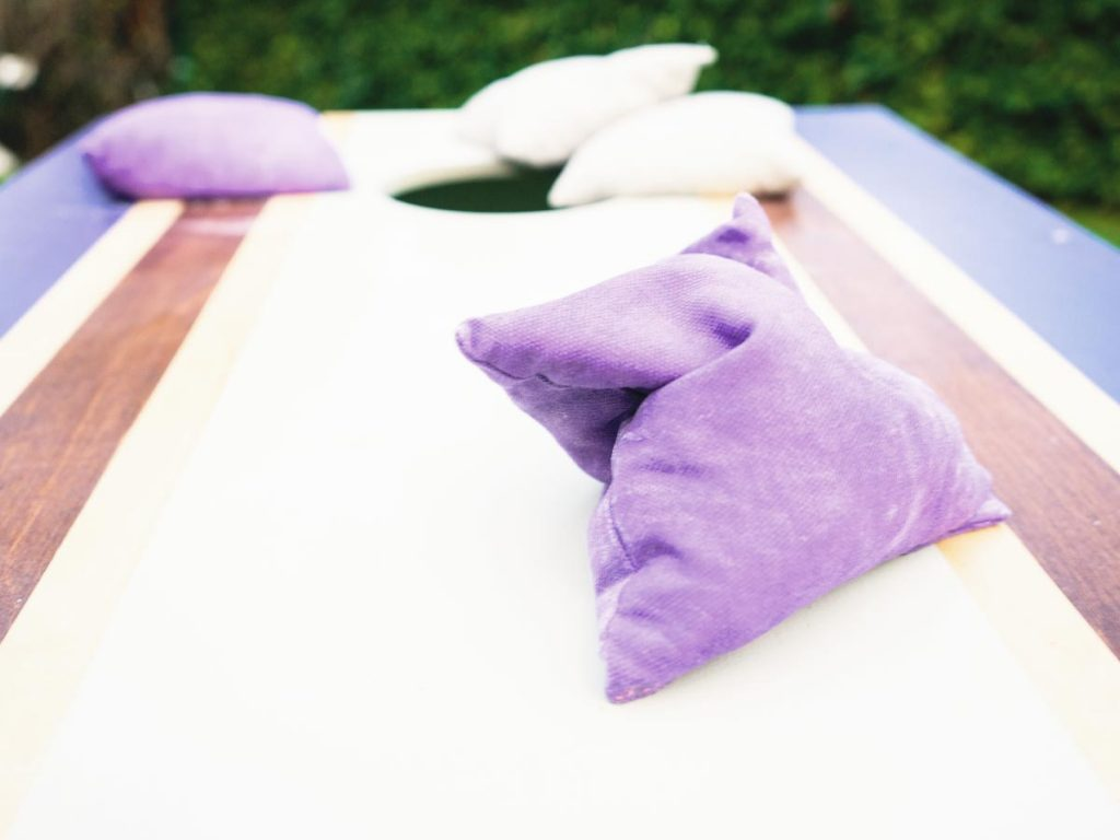 Closely cropped photo of a cornhole game with white and purple bean bags.
