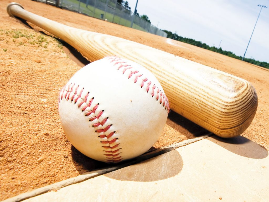 Close-up photo of a baseball and bat lying on the home plate