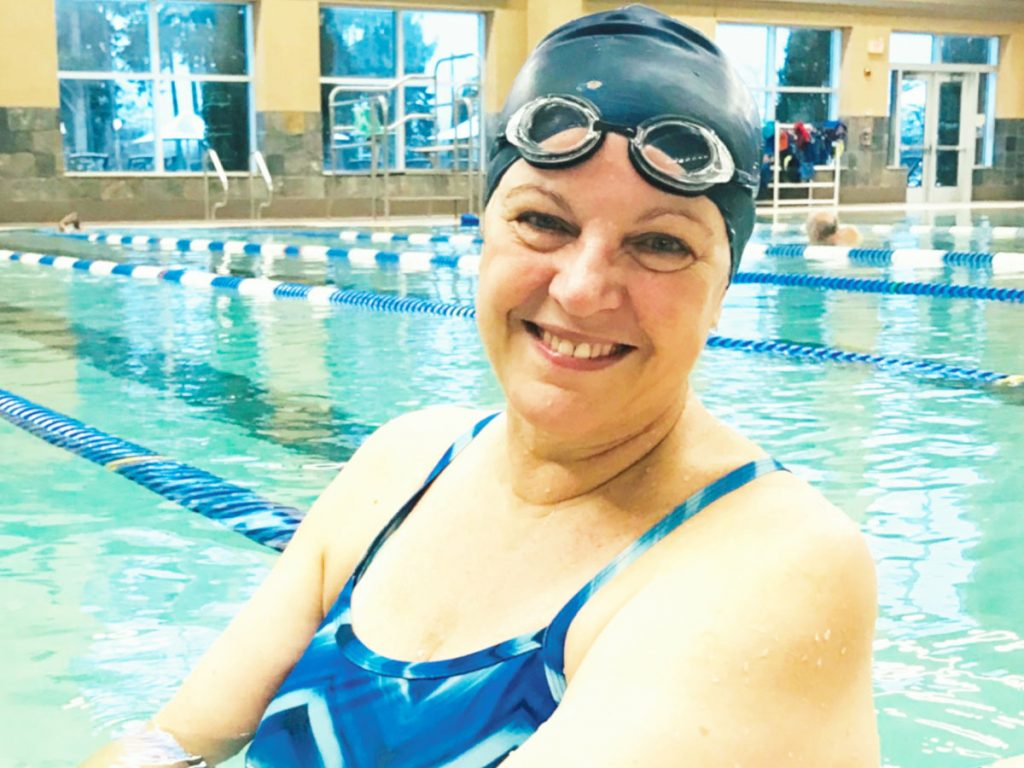 Photo of woman wearing a swim mask while standing in a swimming pool.