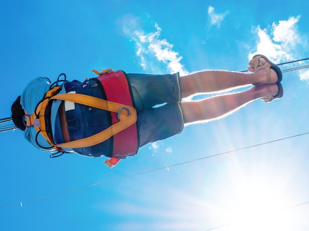 View looking up at someone riding a zipline