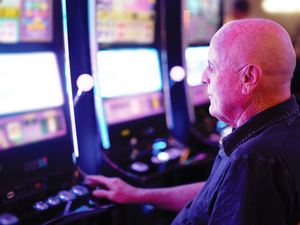 Photo of senior man sitting at a row of slot machines