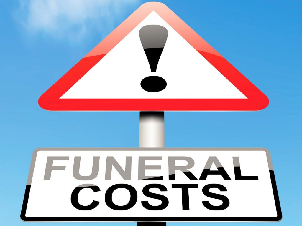 """Photo illustration of a road sign with an exclamation point and text reading, """"Funeral Costs"""" against a blue sky."""