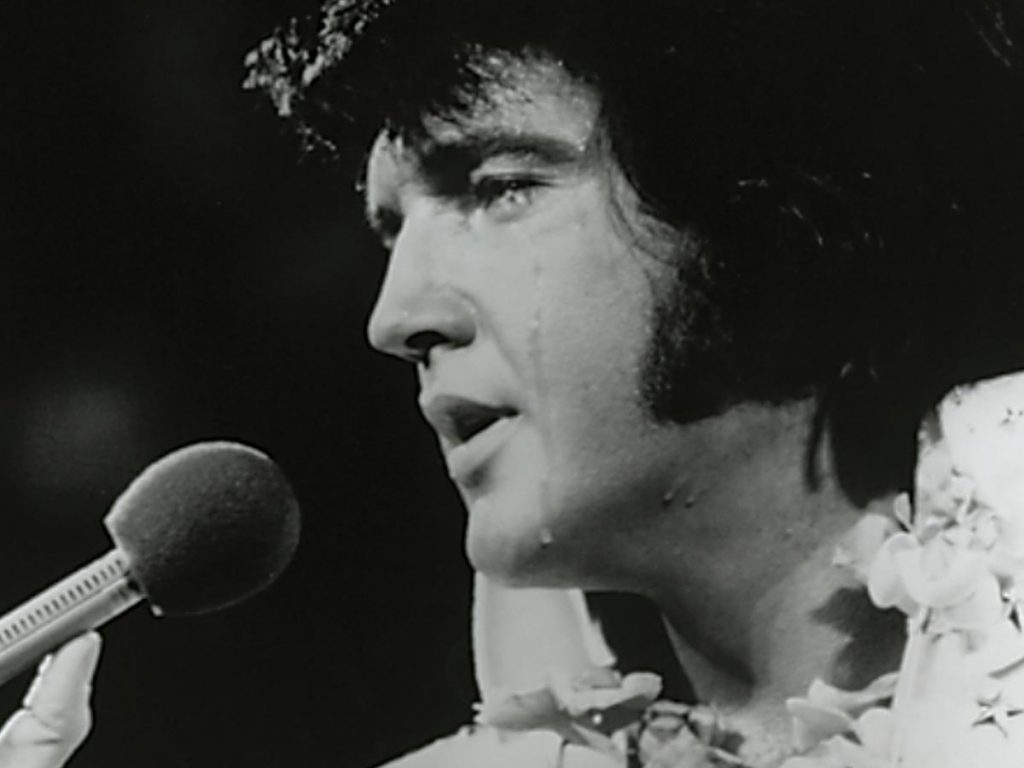 closeup of Elvis Presley singing into a microphone